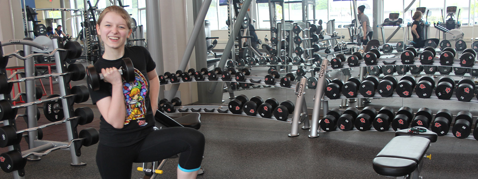 Image of student holding free weights in gym